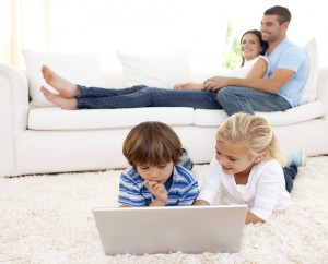 Children using a laptop and parents lying on sofa